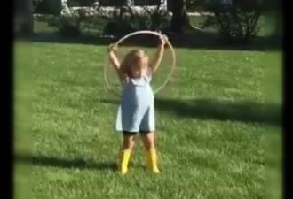 Маленькая девочка пытается крутить обруч